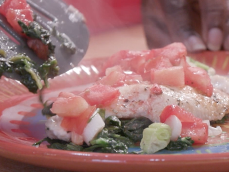 Baked fish with spinach, tomatoes, and onions sits on a plate.