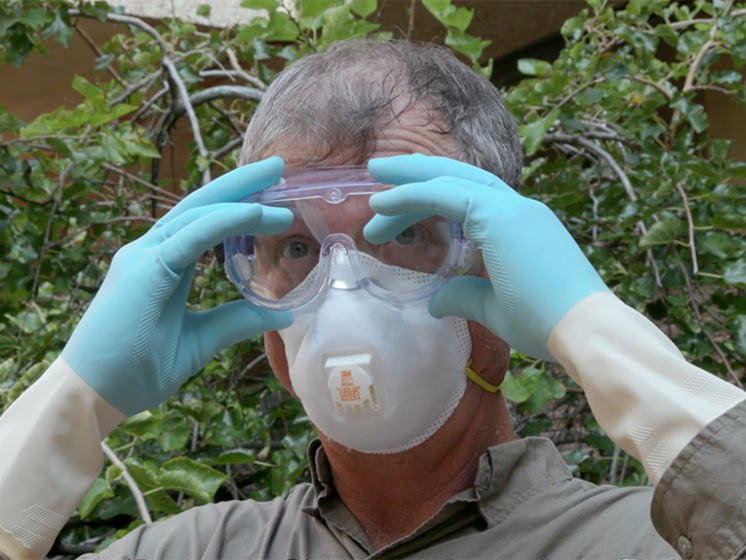 A man prepares for cleaning floodwater damage by wearing rubber gloves, a face mask, and goggles.