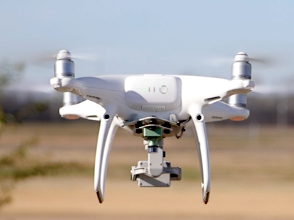 A close up shows a drone hovering above an open field.