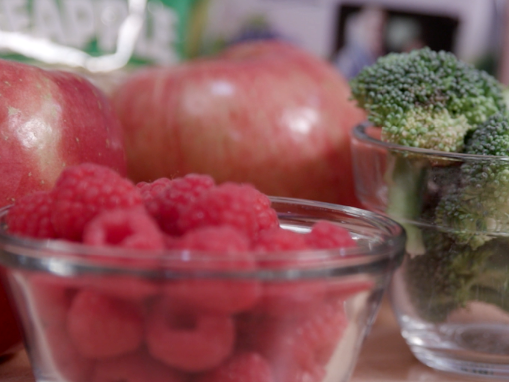 A display of produce including red raspberries in a small clear glass bowl, green broccoli florets in a small clear glass bowl, 2 red apples behind the bowls. Does that work?
