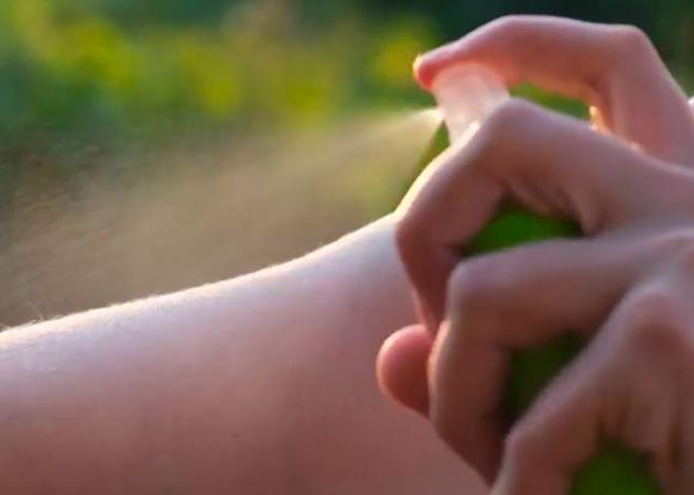 Closeup of someone spraying mosquito repellent on their arm.