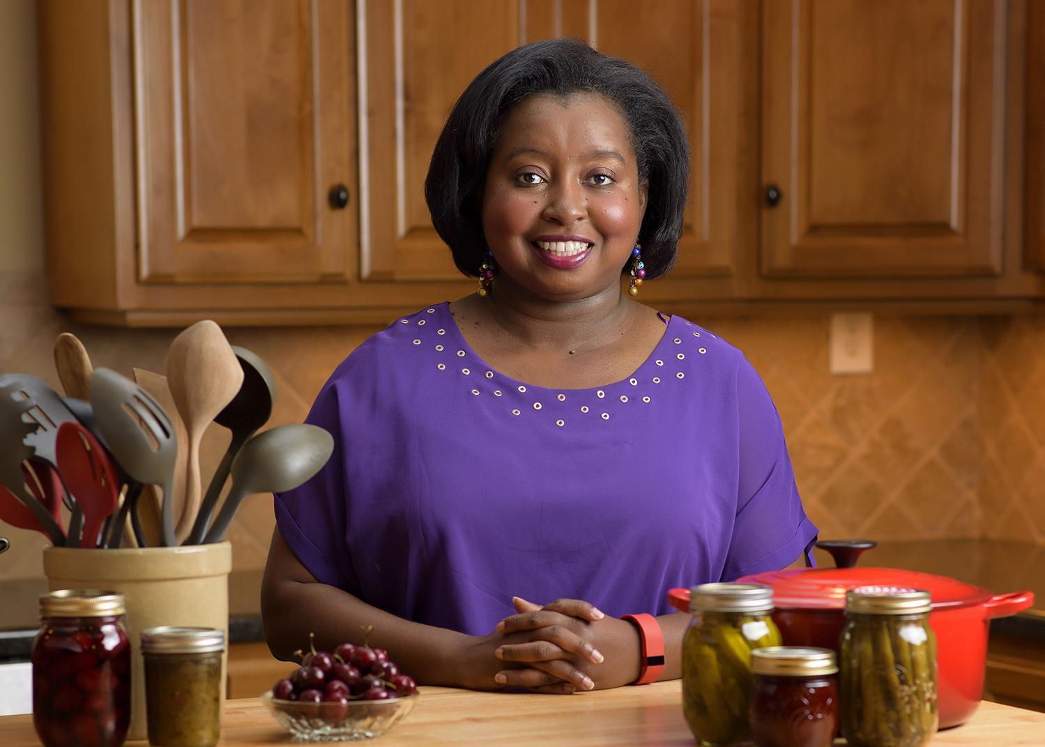 MSU Extension Agent Natasha Haynes, an African American woman with chin-length straight black hair stands behind a kitchen table displaying a crock of kitchen utensils, a red pot, and assorted home-canned and fresh fruits and vegetables.