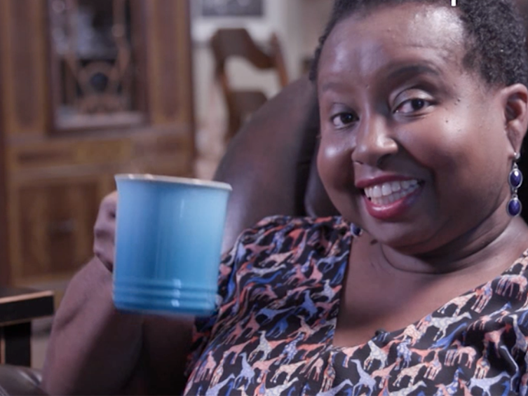 A woman holds up a turquoise blue mug while sitting on a brown leather couch and smiling at the camera.