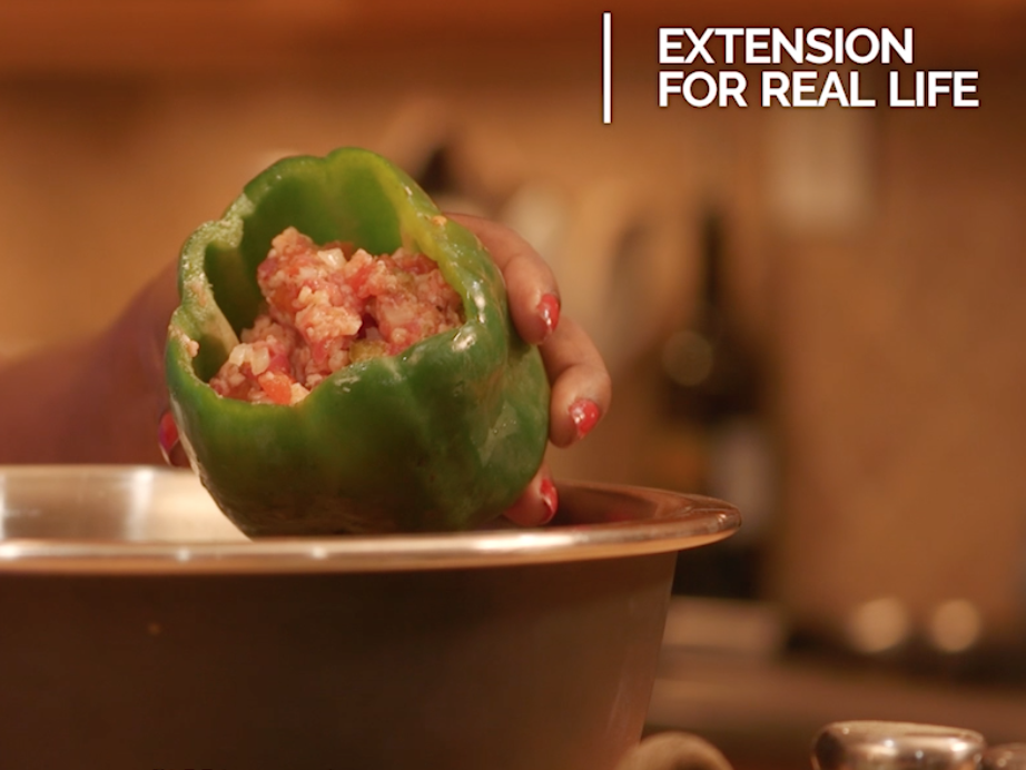 Hands spoon a ground meat and riced cauliflower mixture into a raw green bell pepper held over a stainless steel bowl.