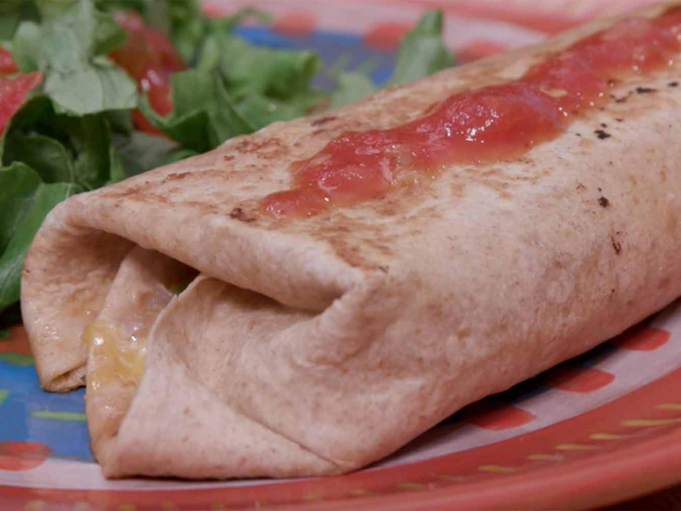 A grilled burrito topped with salsa and a green salad with tomato served on a multicolored plate.