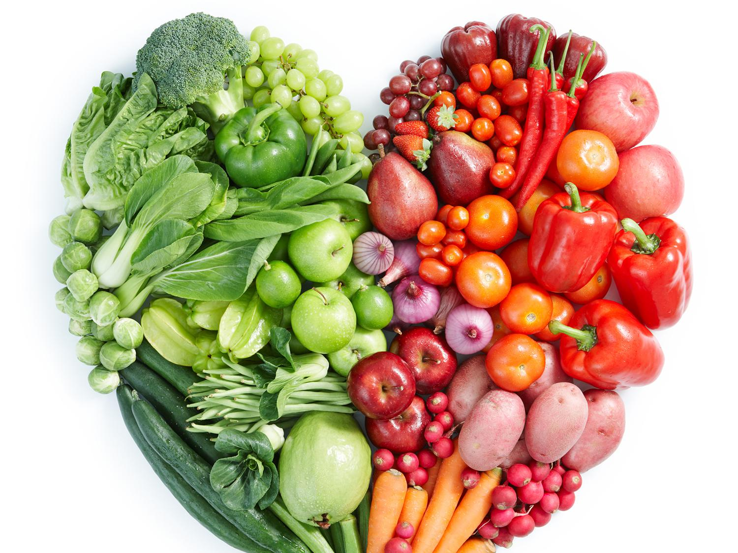 An assortment of green, orange, and red vegetables are arranged in a heart shape.