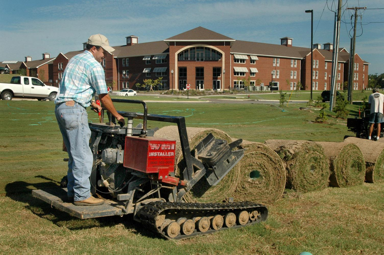 Steve Hughes lays down sod near one of Mississippi State University's new residence halls.  Hughes Sod Installation, of Lee County, placed about 10,000 yards of sod on the campus the week before MSU hosts the first football game of the 2007 season.  (Photo by Linda Breazeale)