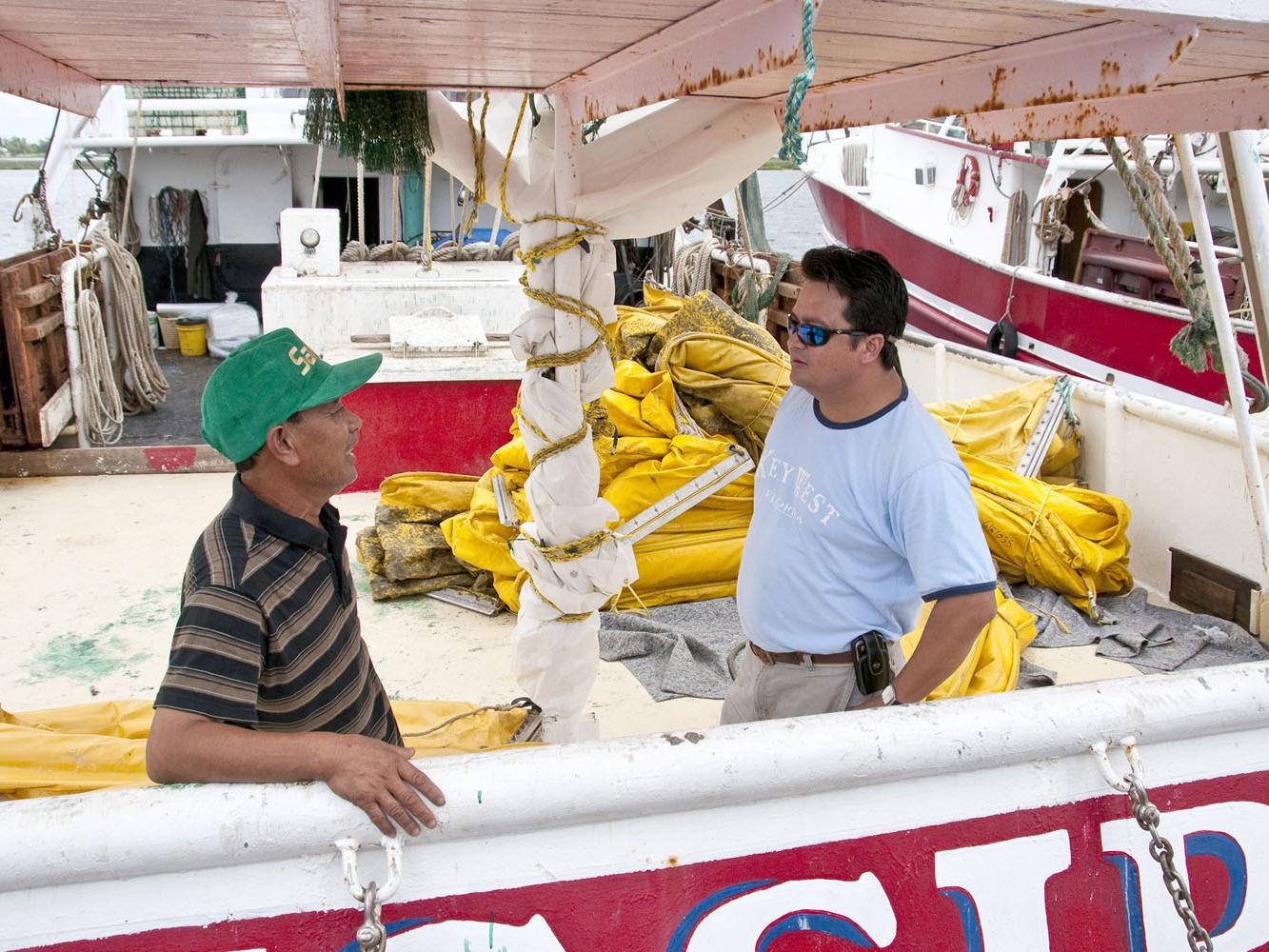 Phat Le, captain of the Mississippi III, discusses cleanup of the Deepwater Horizon oil spill with Extension Fisheries Technician Peter Nguyen. Many fishermen and shrimpers are working as oil spill cleanup contractors for BP. (Photo by Scott Corey)
