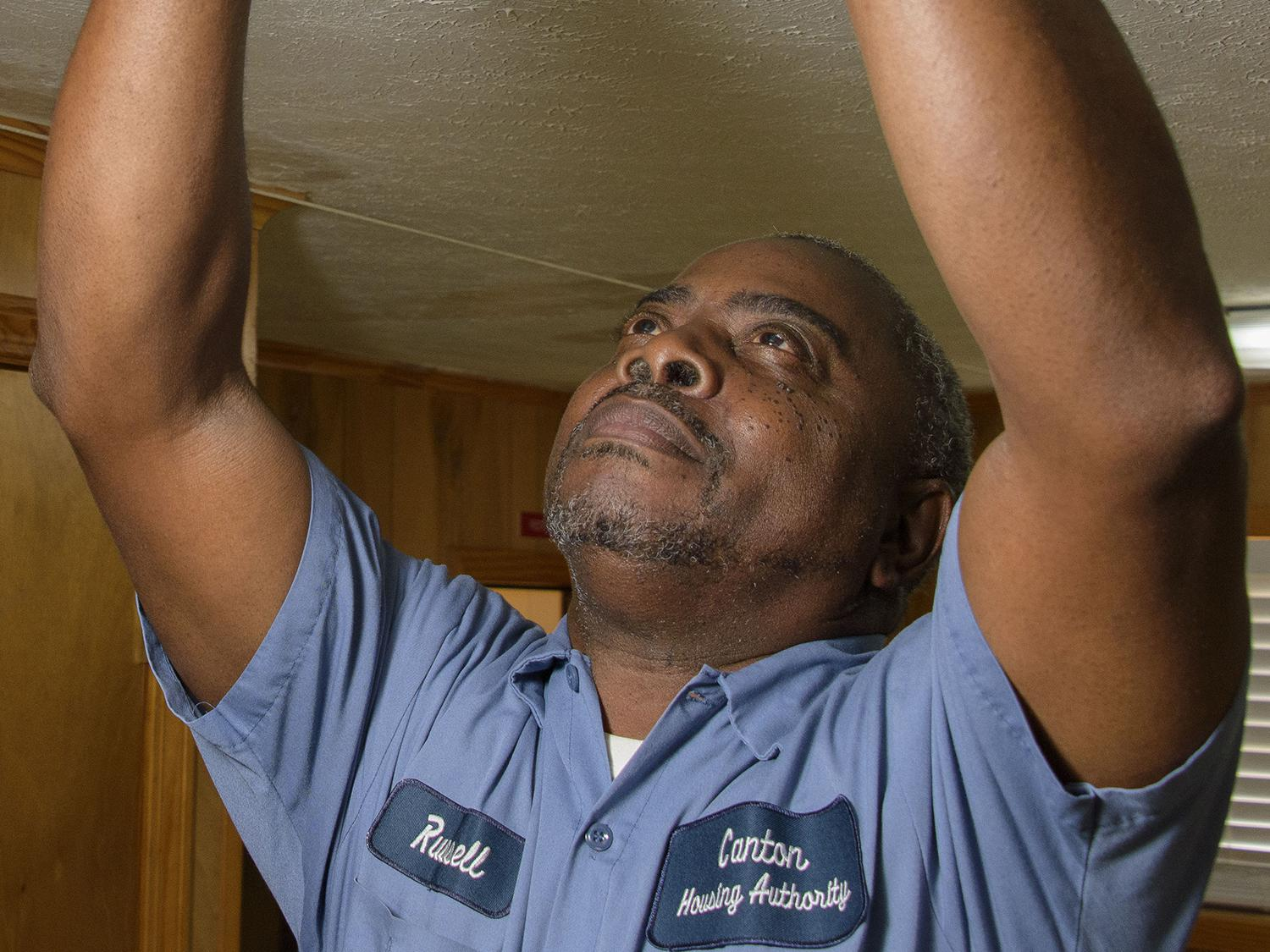 Russell Carroll, a maintenance supervisor with the Canton Housing Authority in Canton, Mississippi, checks batteries in a smoke detector in one of the housing units he services. Carroll participated in a Healthy Homes Initiative training and shares information with his colleagues and clients to help them improve their environments. (File photo by MSU Extension Service/Kevin Hudson)