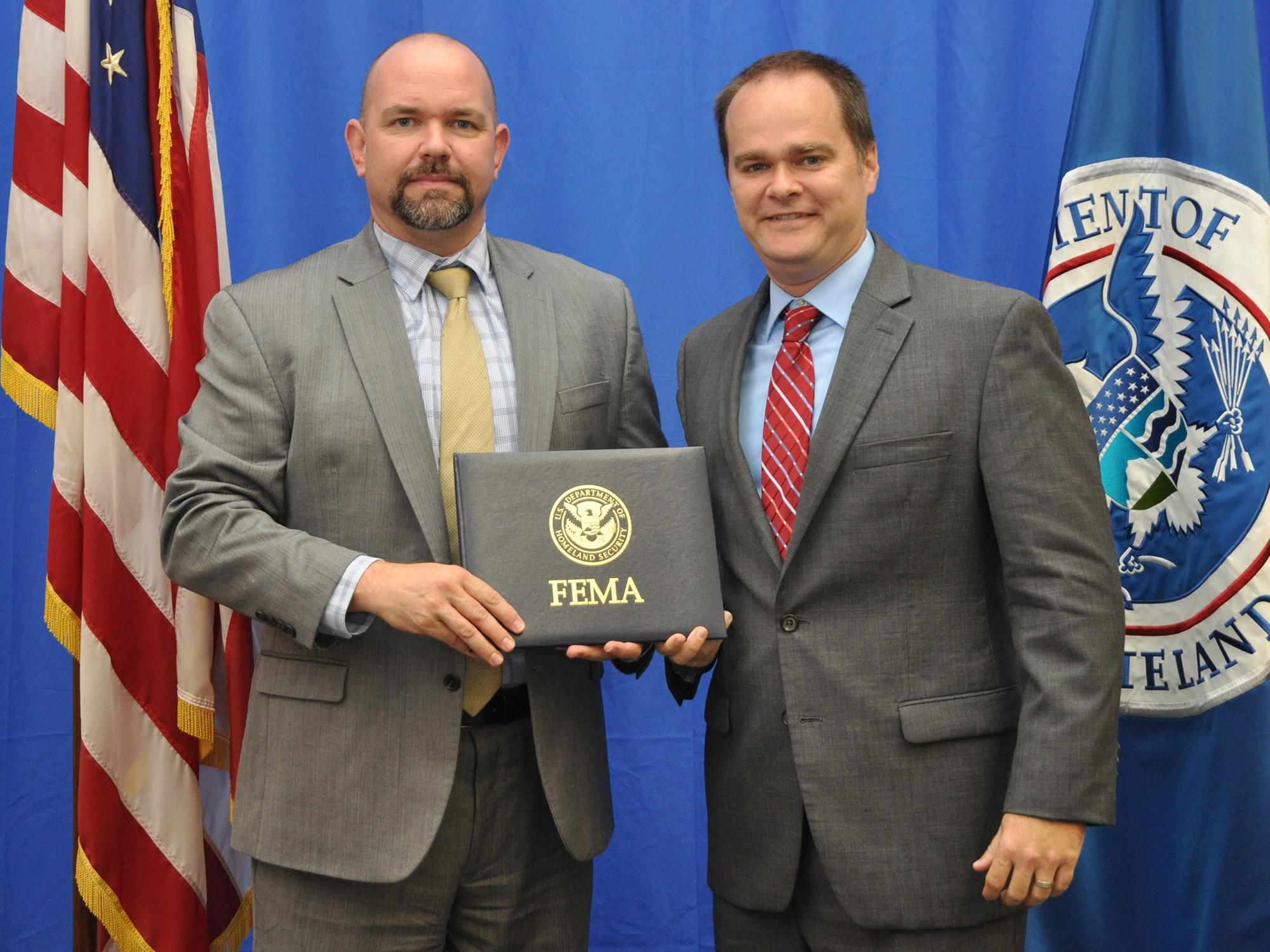Two men on a stage holding a FEMA certificate and looking at the camera.