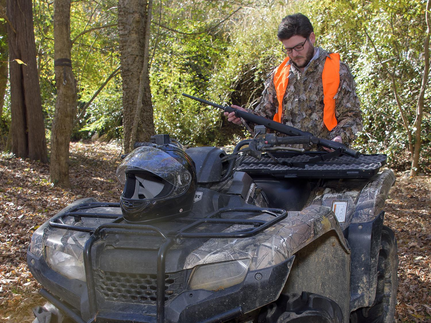A hunter in camouflage and an orange vest places his rifle into storage on the back of an ATV in the woods.