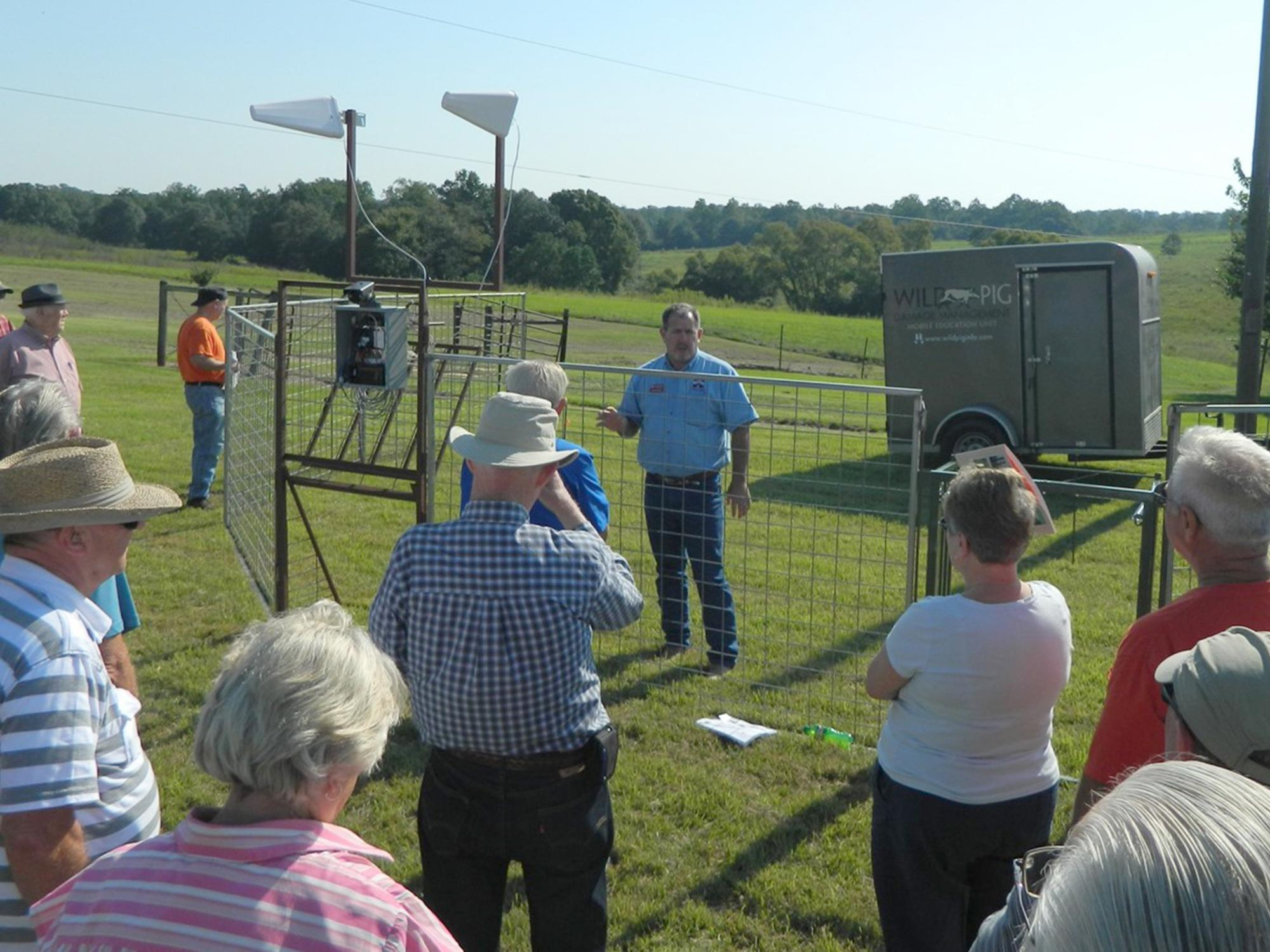 A group of adults gather outside a metal corral with electronics attached to it with a speaker inside the trap.