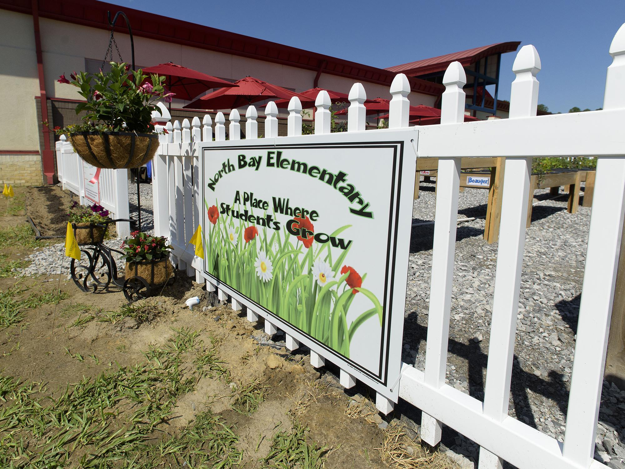 Colorful flowers are planted next to a sign at the entrance of the North Bay Elementary School garden.