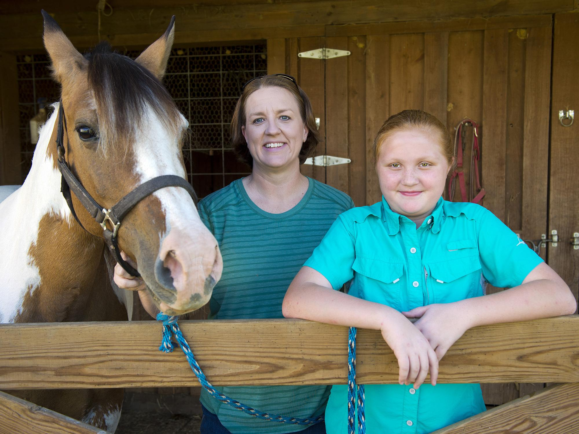 A young girl and her mother are pictured with their horse.