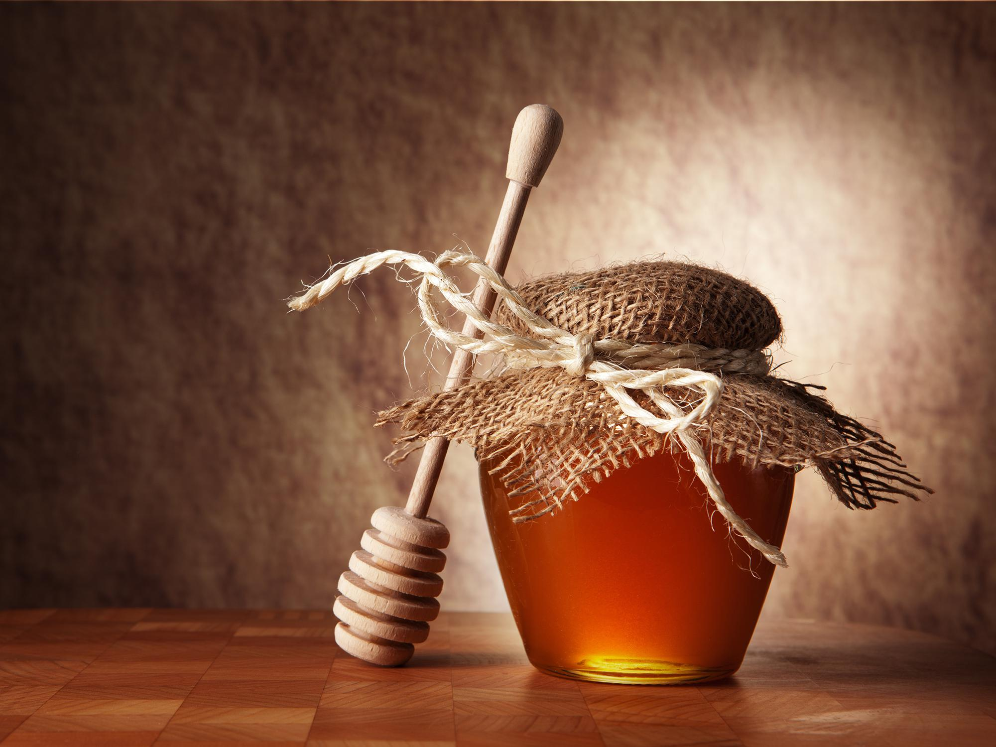 Wooden honey dipper lying against a small jar of honey that is covered with a decorative piece of fabric tied with a string.