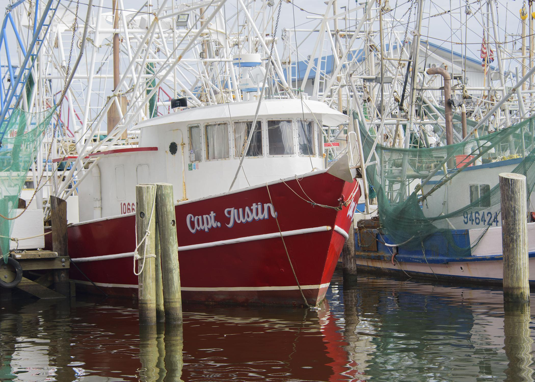 A red shrimp boat with similar boats behind and beside it.