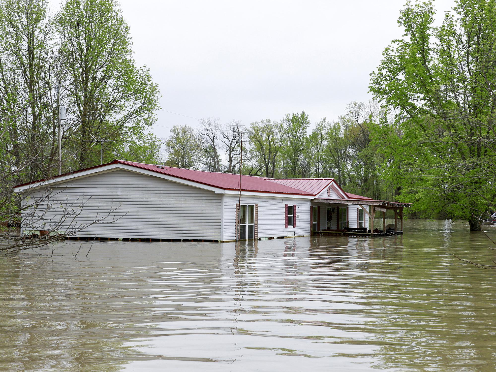 A gray, double-wide manufactured home with flood waters reaching the lower windows and surrounding area