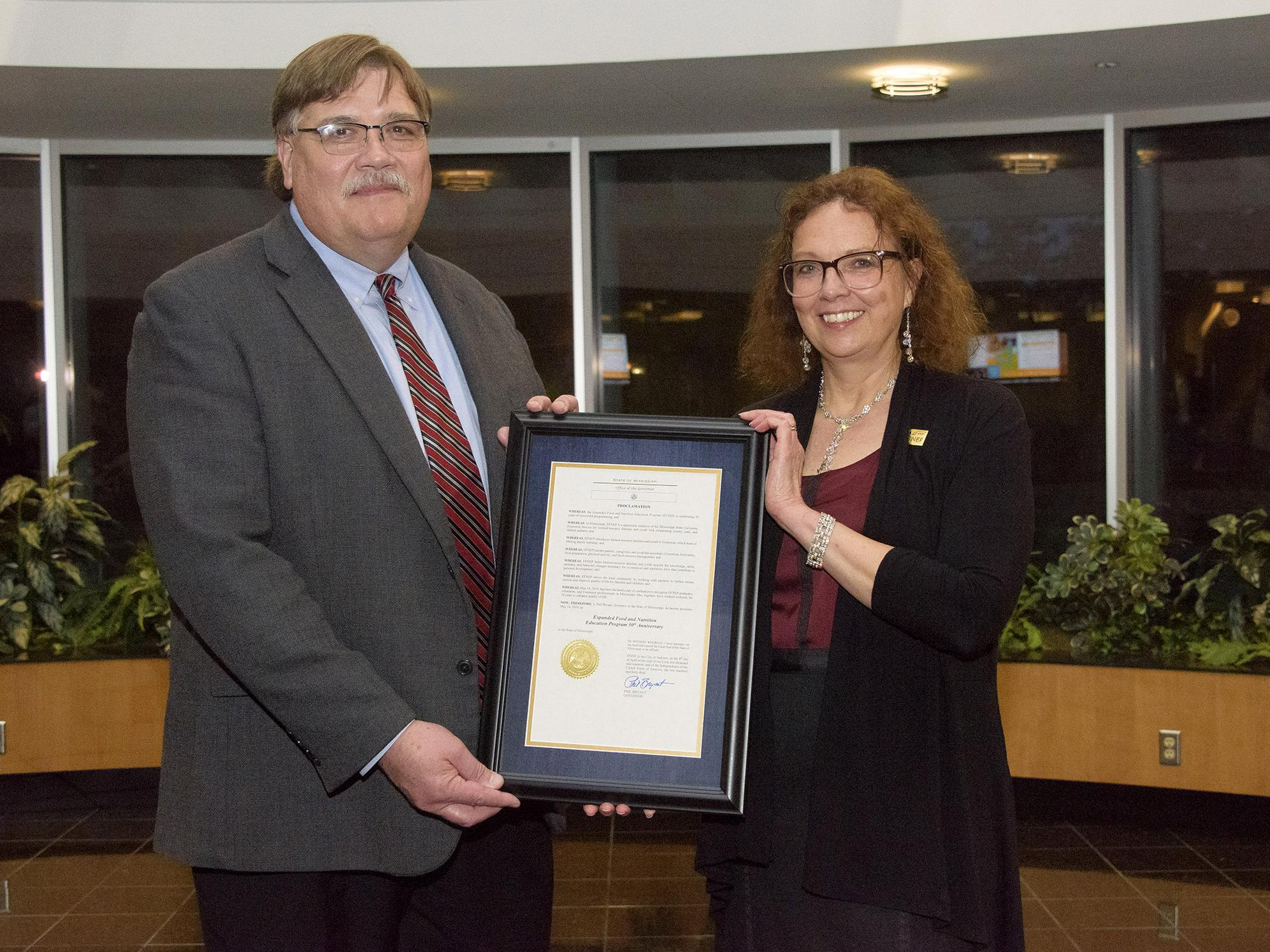 A man on the left and a woman on the right stand in an atrium and hold a framed document with a gold seal.