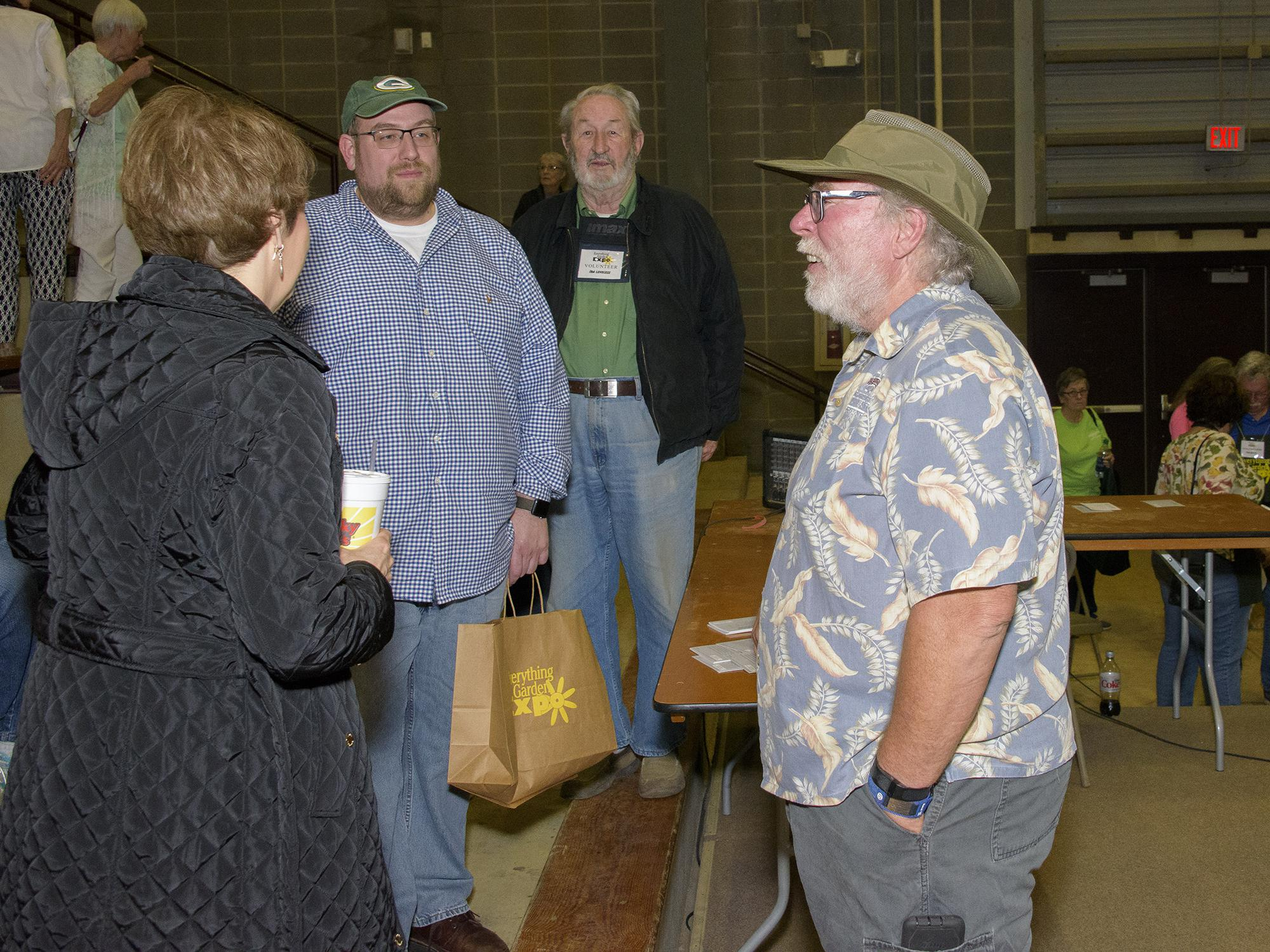 A man in a gardening hat stands and talks to three adults, with several others milling about in the background.