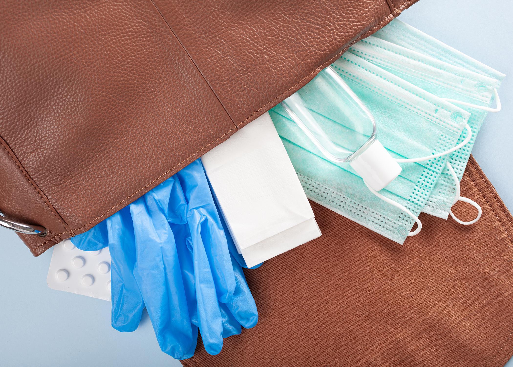 Protective medical mask, sanitizer gel and gloves in bag.