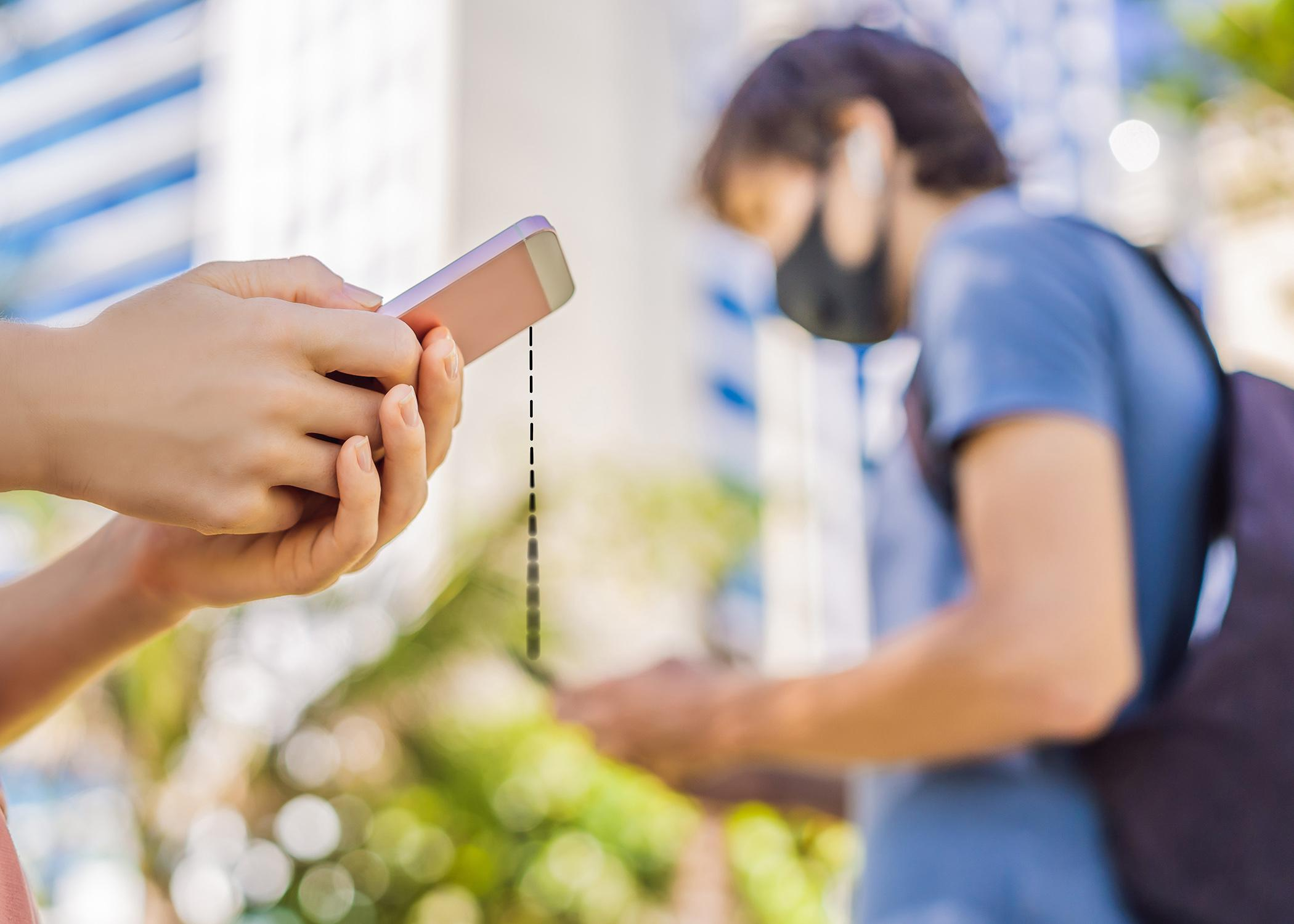 People wearing face masks holding cell phones