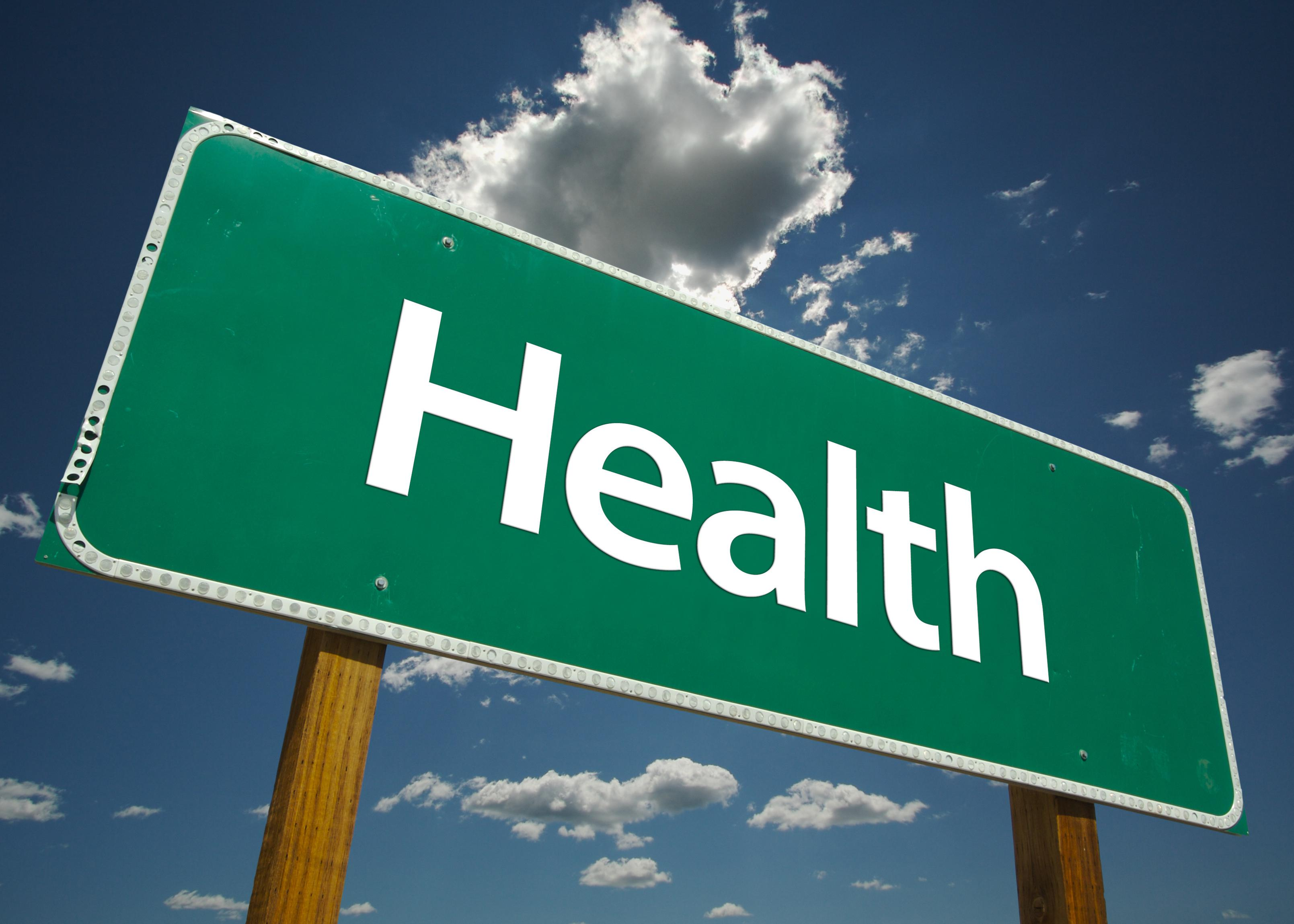 "A green road sign with the word ""Health"" is pictured against a blue sky with white clouds."