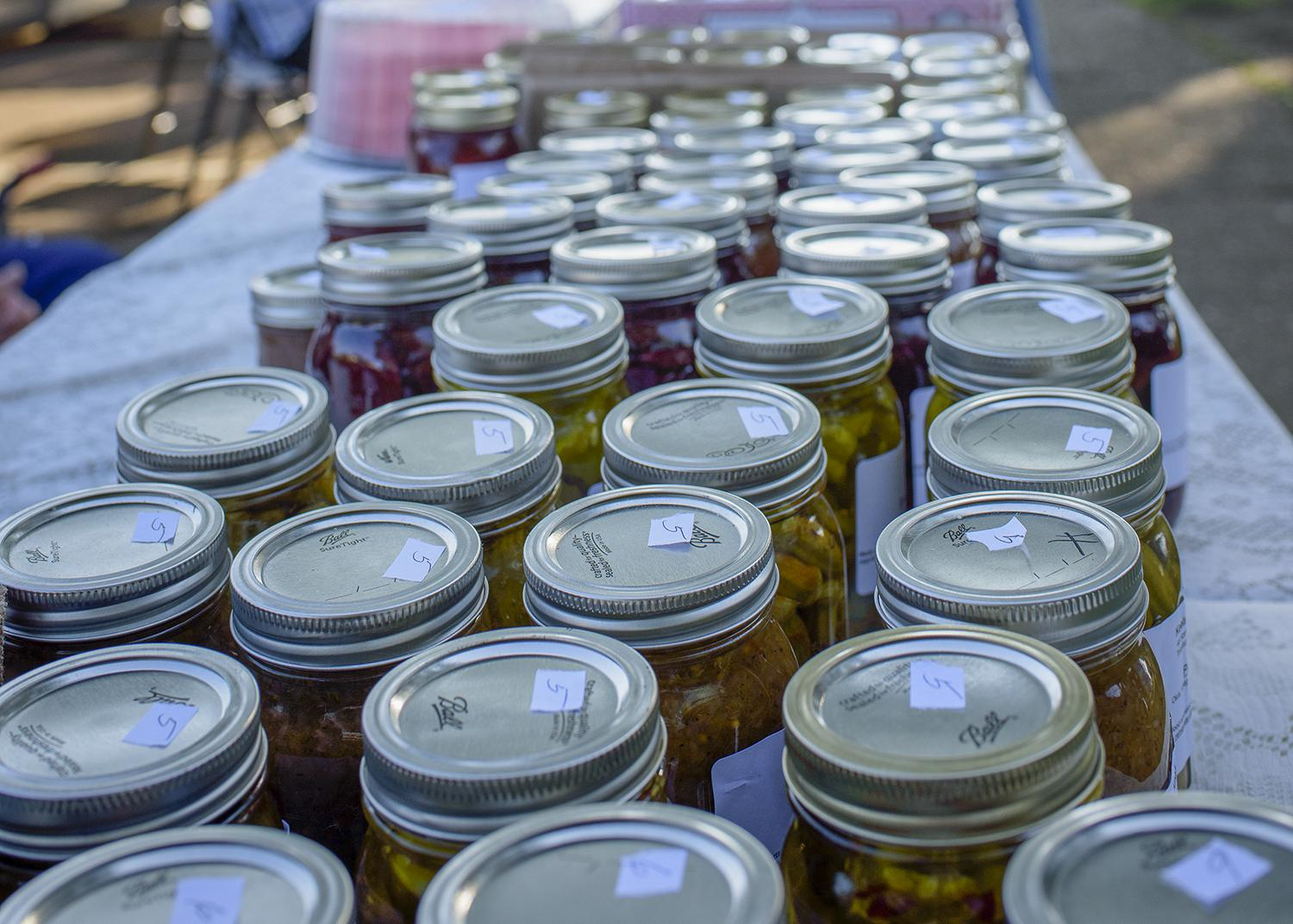 Rows of canning jars line a table at an open-air marketplace.
