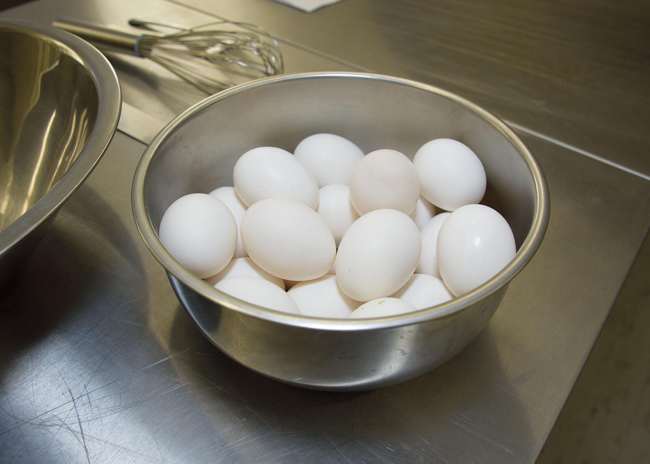 Several eggs sit in a bowl on a kitchen counter.