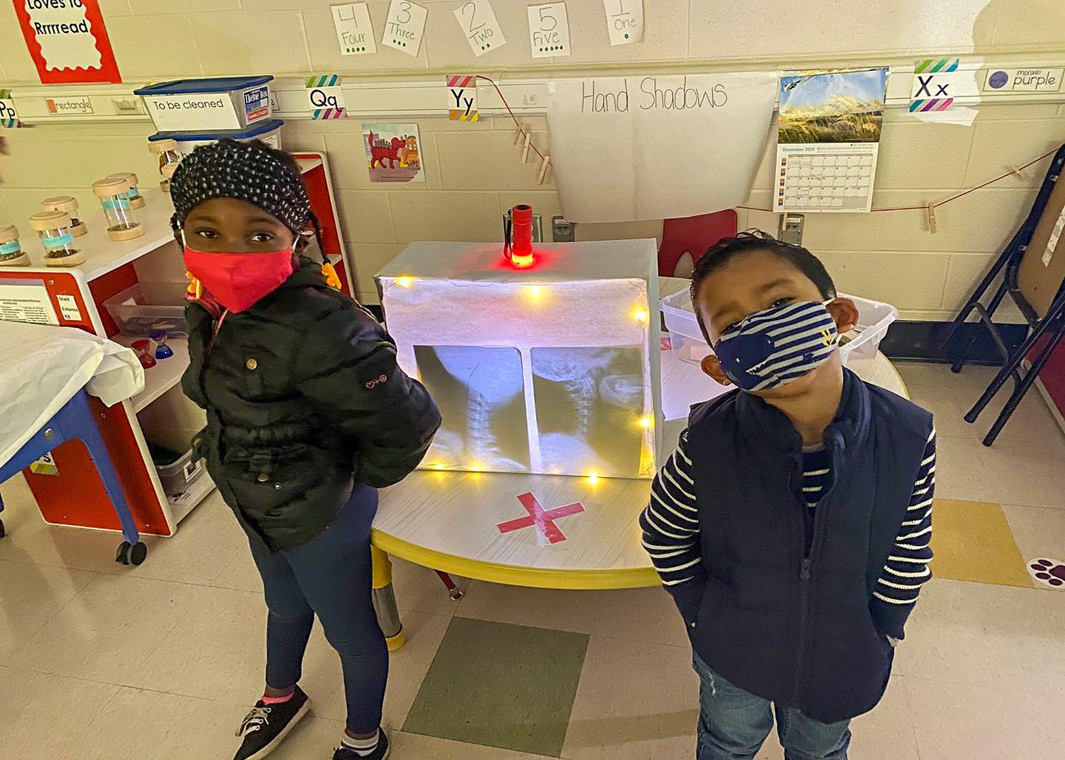 Two children in masks stand in front of an activity center in a classroom.