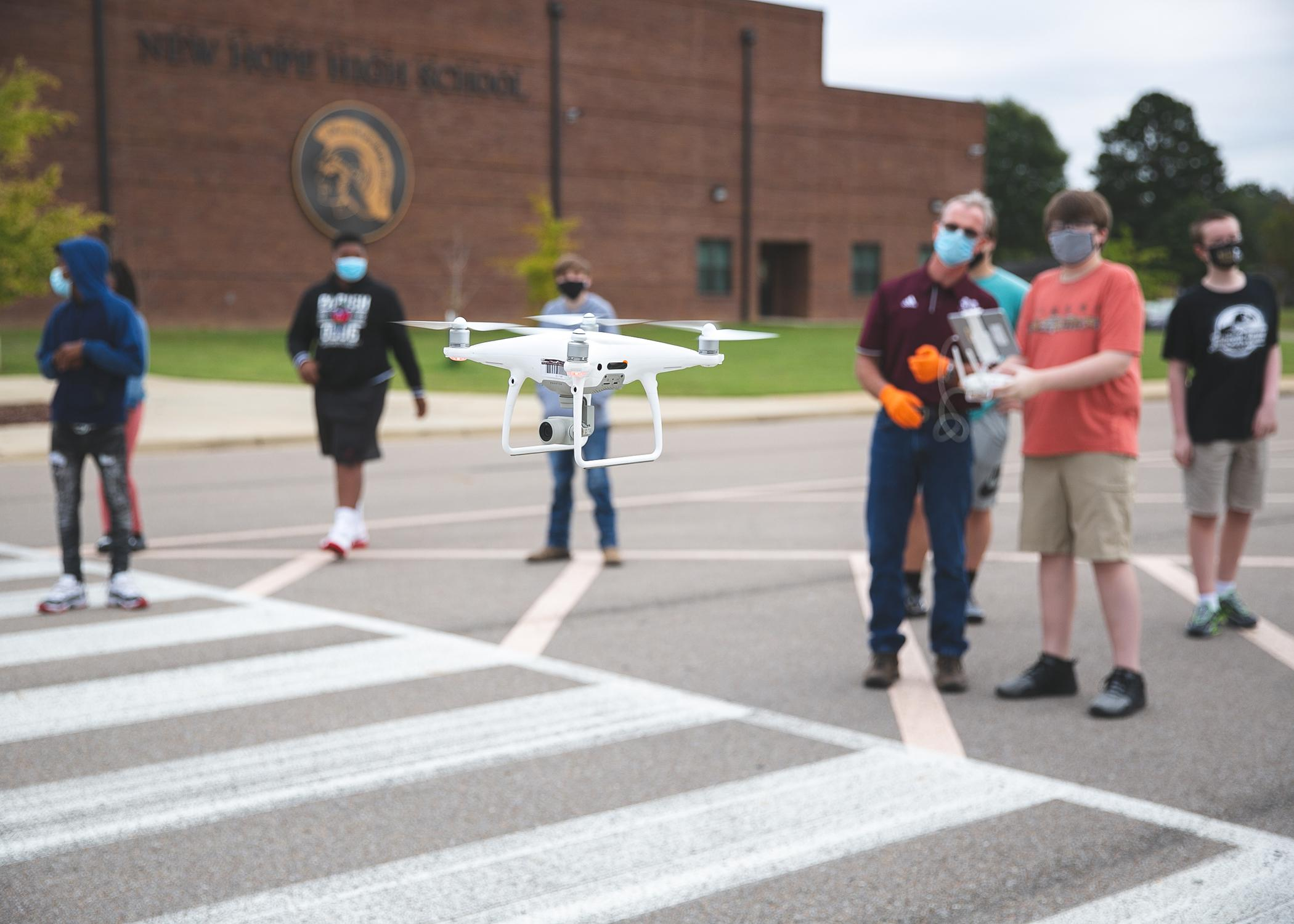 A drone in the foreground being controlled by young students in the background.