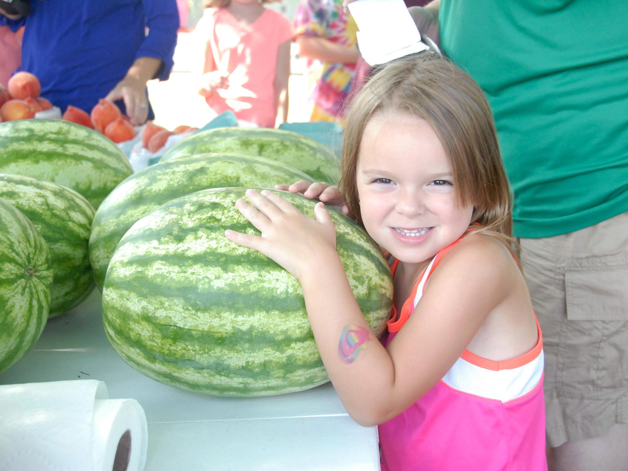 Emily Grace Barnette is ready to take this watermelon home from the Starkville Community Market on June 21, 2016. (Photo by MSU Extension Service/Linda Breazeale)
