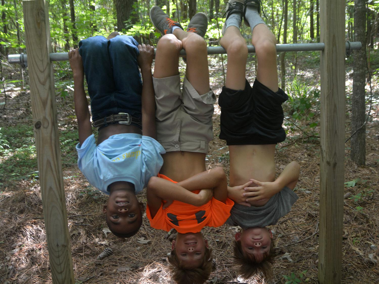 Imitating bats that like to hang upside down is a fun activity for children as they explore a nature trail at St. Catherine Creek National Wildlife Refuge near Natchez, Mississippi, on July 7, 2016. (Photo by MSU Extension Service/Linda Breazeale)