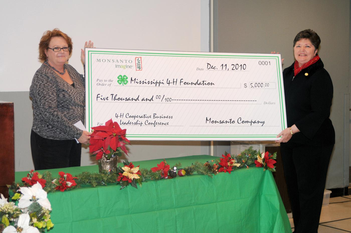 Monsanto Co. representative Derenda Stanley, left, presents Susan Holder a ceremonial check for $5,000 in support of 4-H. Holder, director of the 4-H Youth Program with the Mississippi State University Extension Service, said the funds will support the 4-H Cooperative Business Leadership Conference in 2011. This annual event is the reward given to senior-level 4-H members who placed first in their state competitions at 4-H Congress and state 4-H leadership team members. The primary objective of grants from