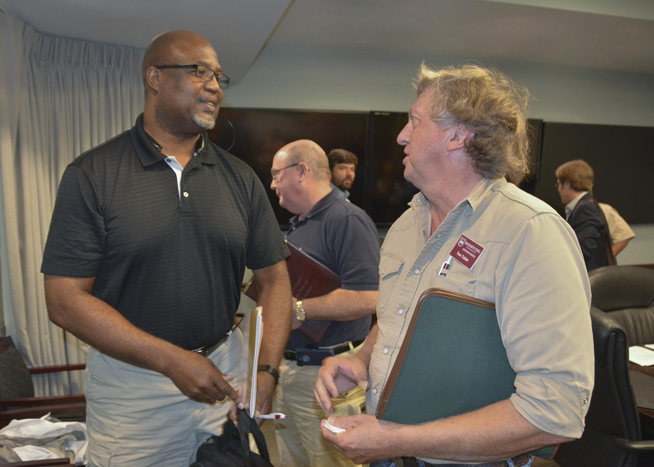 Greg Walker, director of human resources for Mar-Jac Poultry, left, talks to Tom Tabler, a poultry specialist with the Mississippi State University Extension Service, during a bird flu information meeting at the Mississippi Emergency Management Agency office in Pearl on Sept. 11, 2015. (Photo by MSU Ag Communications/Linda Breazeale)