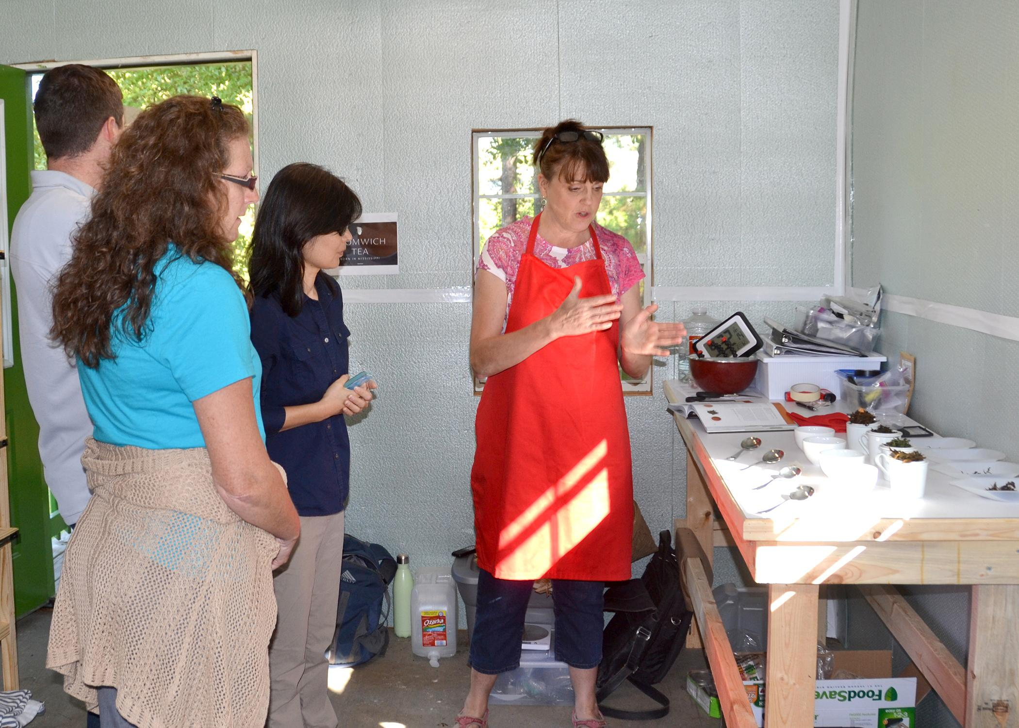 Donna Beliech, horticulture agent with the Mississippi State University Extension Service; Judson Lecompte, MSU research associate, and Guihong Bi, MSU associate research professor, listen as tea blender Beverly Wainwright explains the process of developing tea blends at The Great Mississippi Tea Company in Brookhaven, Mississippi, on Oct. 2, 2015. Wainwright is working with other tea consultants to make unique tea blends for the company. (Photo by MSU Ag Communications/Susan Collins-Smith)
