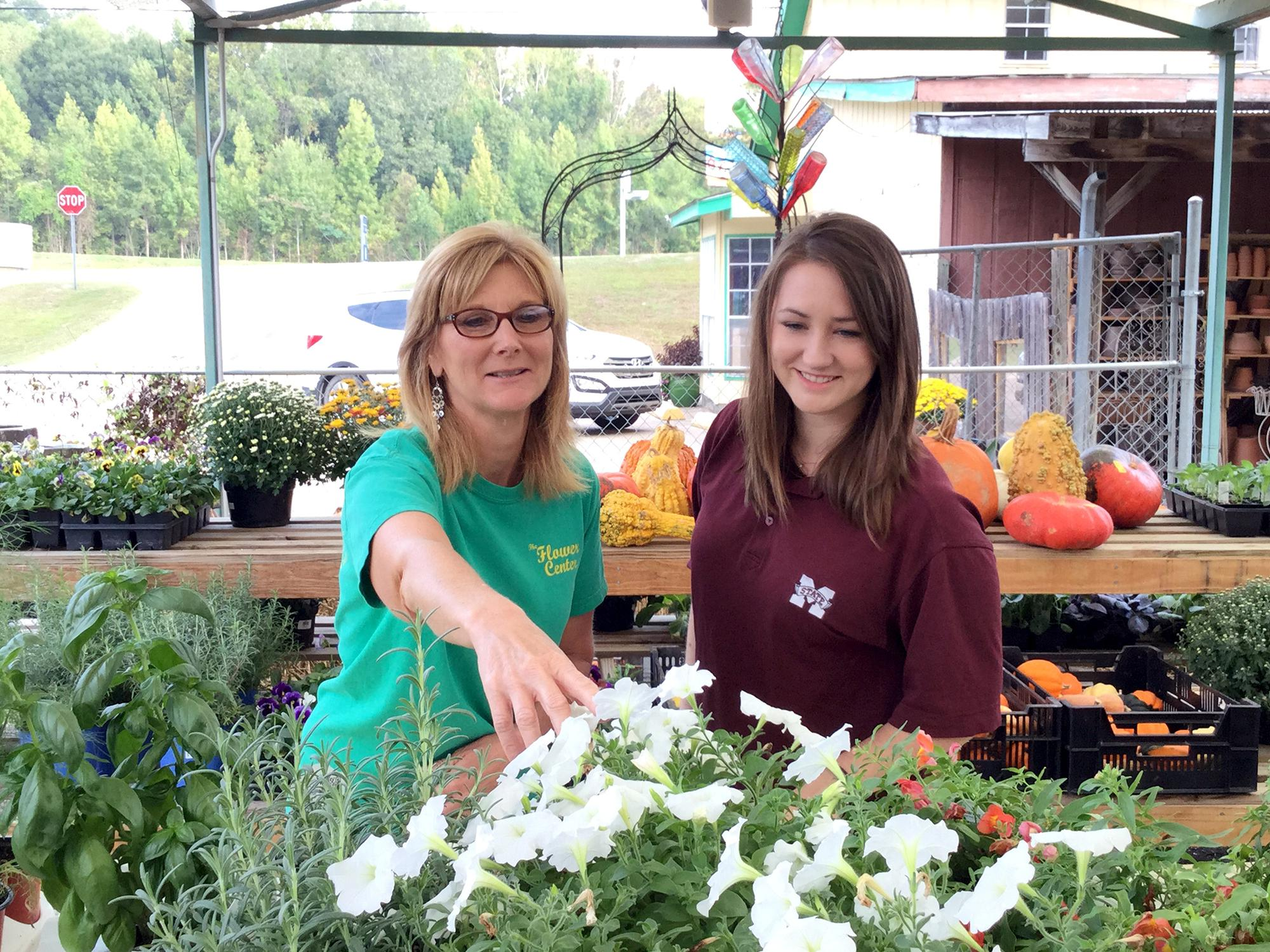 Libby Beard, co-owner of The Flower Center in Vicksburg, Mississippi, left, and Anna McCain, Warren County Extension agent, look over some of the fall bedding flowers available on Oct. 7, 2015. (Submitted photo)