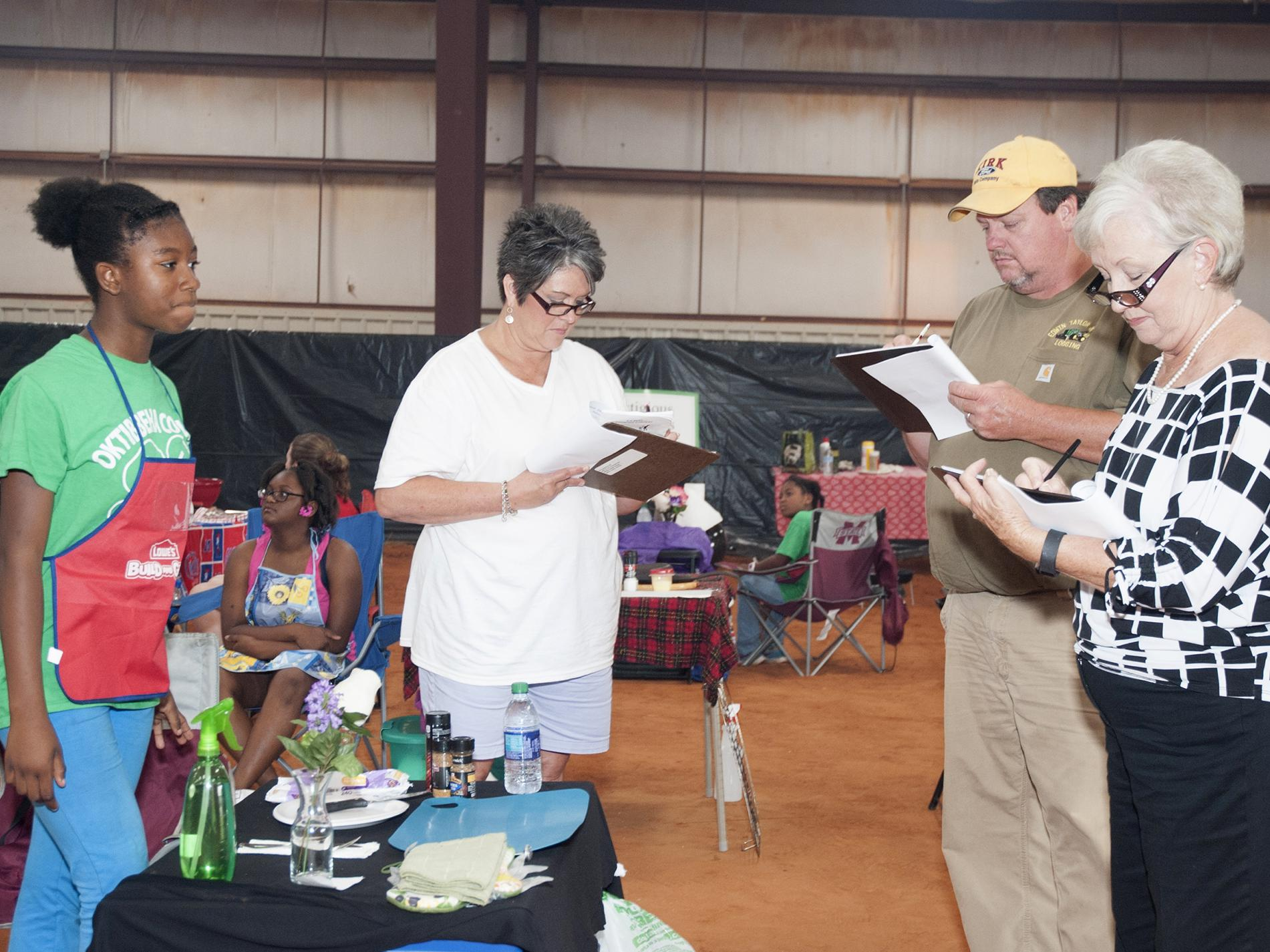 Oktibbeha County 4-H member Trukyra Lawrence, left, waits as judges, from left, Theresa Sproles, Edwin Taylor and Lanelle Martin evaluate her grilling area at the 2016 North Half State Cook-Off competition on June 28, 2016. (File photo by MSU Extension Service/ Kat Lawrence)