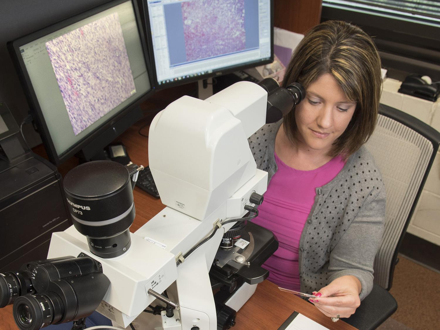 Dr. Alicia Olivier, an assistant professor in the Mississippi State University College of Veterinary Medicine, prepares to view a histology slide from a necropsy under a microscope. MSU offers this service to help determine causes of death for animals. (Photo by MSU-CVM/Tom Thompson)