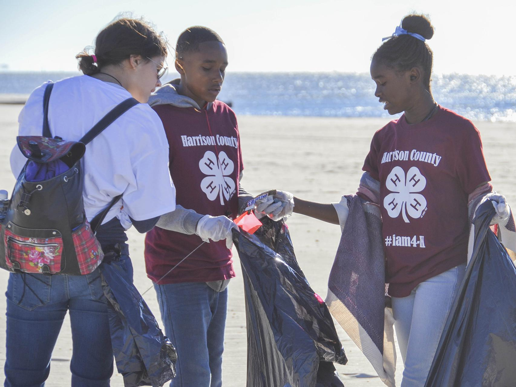 Jessica Lero, left, records the types of trash Kaileb Williams, center, and Laila Williams found while participating in the 2016 Mississippi Coastal Cleanup on Oct. 22 in Biloxi, Mississippi, with their Mississippi State University Extension Service 4-H club in Harrison County. They joined about 2,400 volunteers to collect more than an estimated 10 tons of trash during the 28th annual event. (Photo by MSU Extension Service/Susan Collins-Smith)