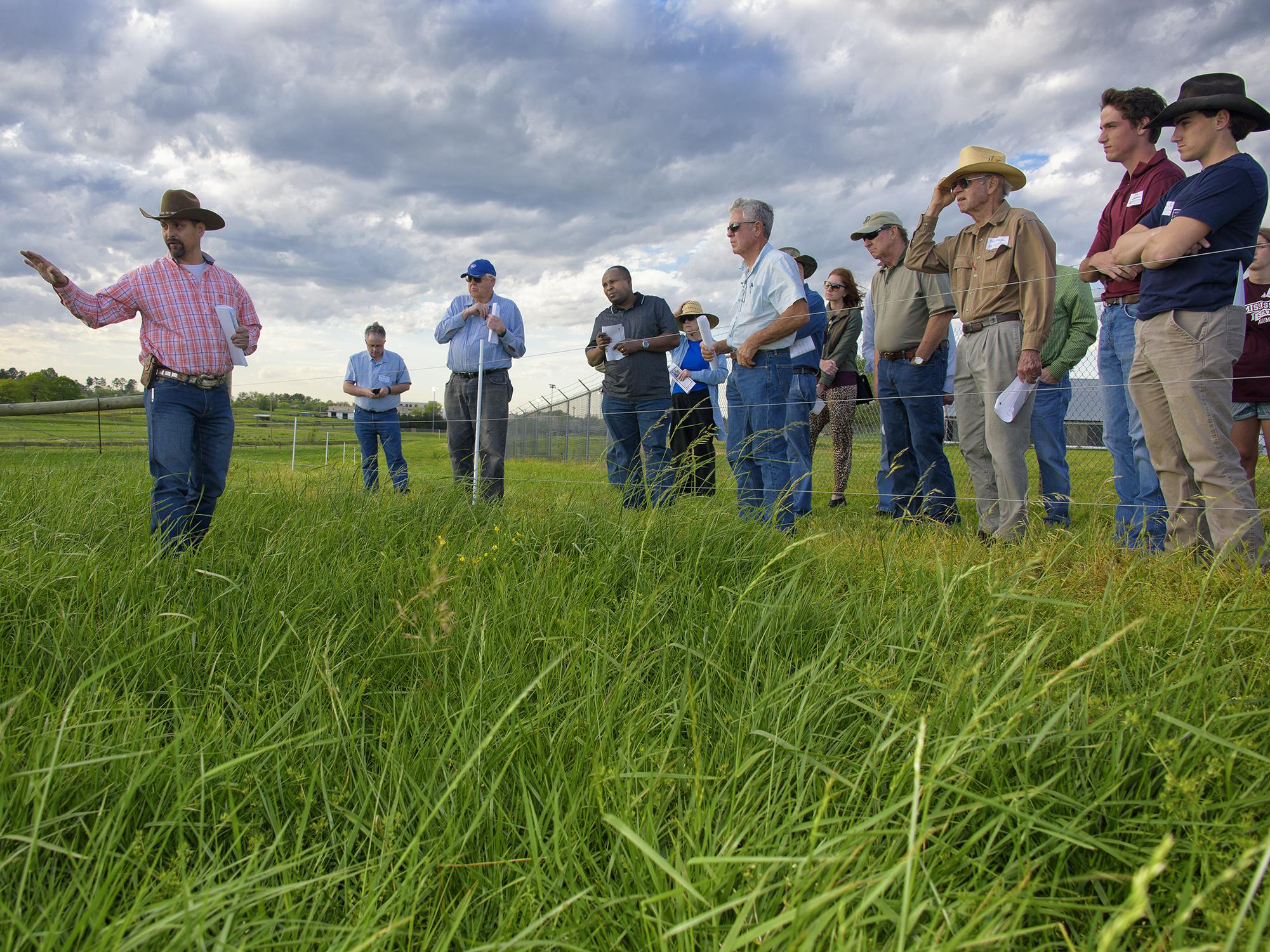 Rocky Lemus (left), forage specialist with the Mississippi State University Extension Service, explains successes and challenges with fescue growing at the H.H. Leveck Animal Research Center. Lemus led tours during a Forage Field Day near Starkville, Mississippi, on April 7, 2016. (Photo by MSU Extension Service/Kevin Hudson)