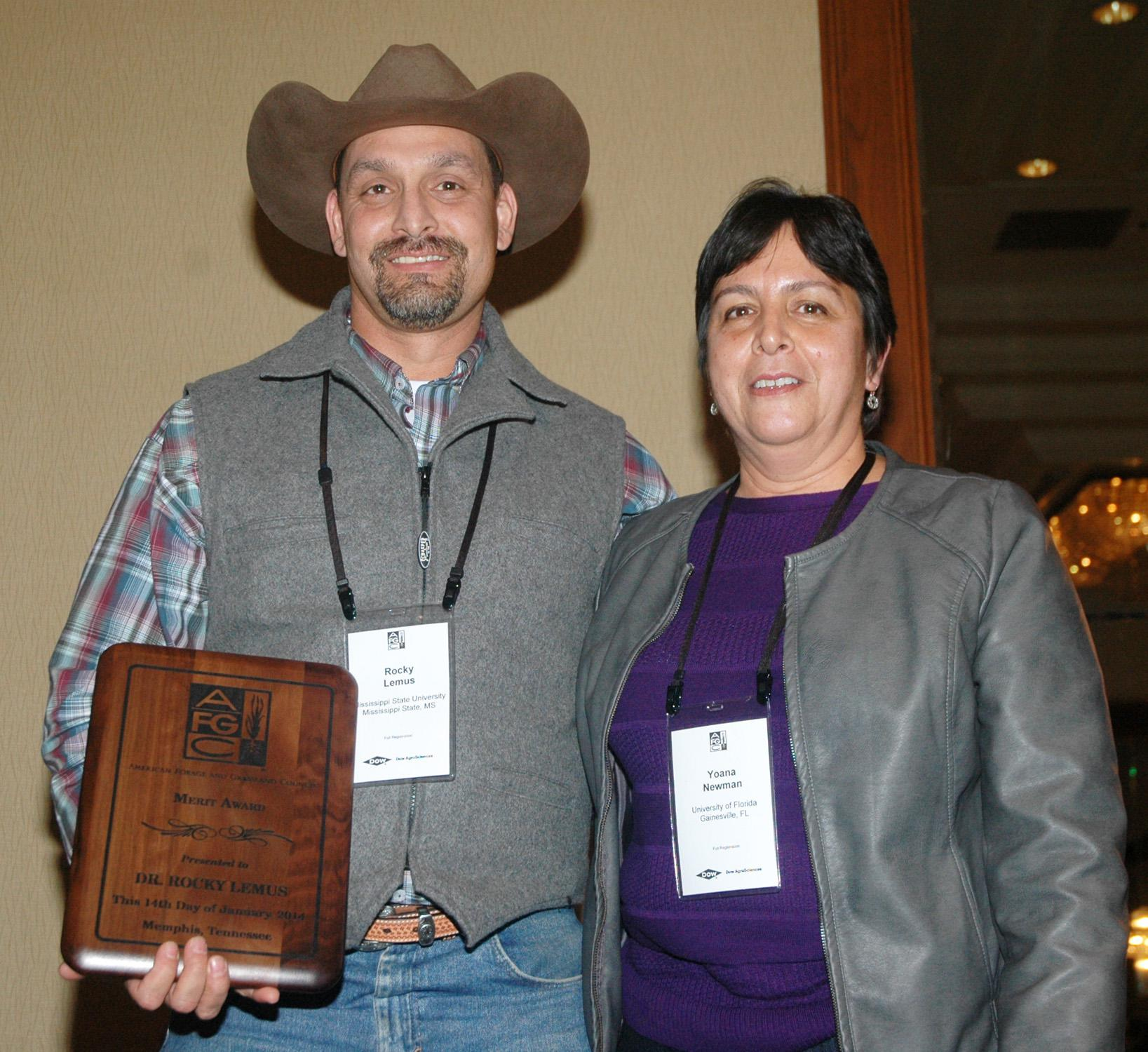 Rocky Lemus receives a merit award from Yoana Newman, a member of the American Forage and Grassland Council Board and Foundation Board, during the recent annual conference in Memphis on Jan. 14, 2014. (Photo by Virginia Tech/Chris Teutsch)