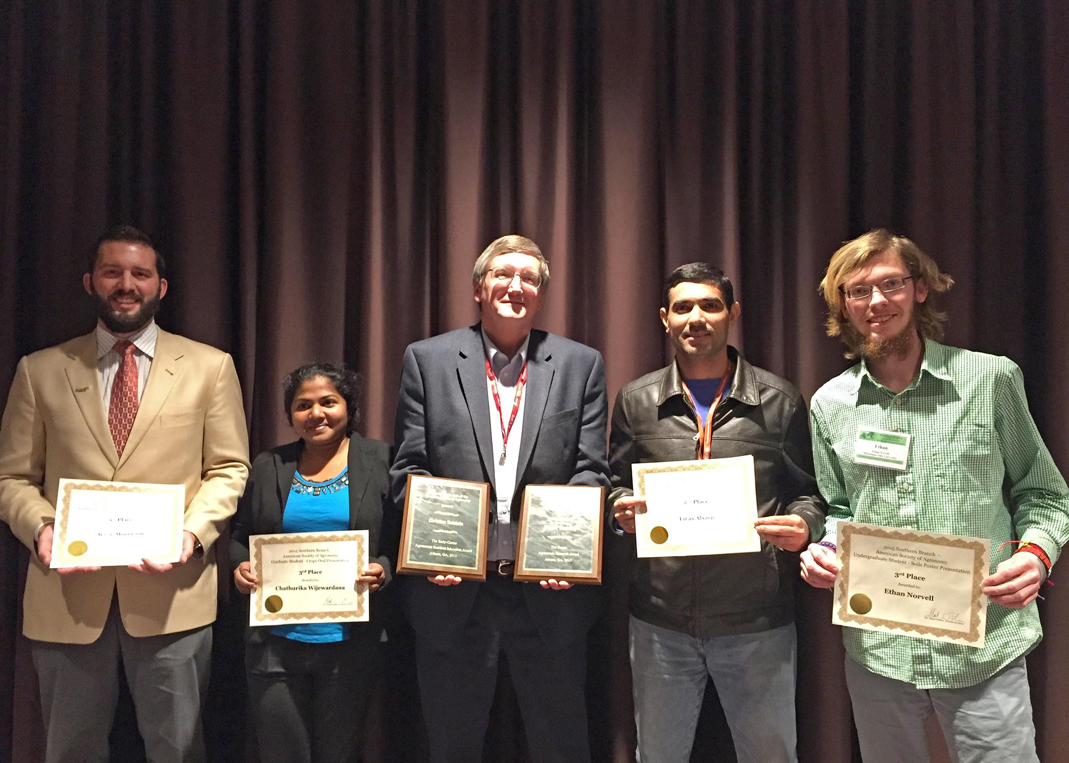 Mike Phillips, center, head of the Mississippi State University Department of Plant and Soil Sciences, joins faculty members and students from his department displaying awards received during a recent meeting of the Southern Branch of the American Society of Agronomy. Pictured are (from left to right) Jesse Morrison, doctoral student; Chathurika Wijewardana, master's student; Phillips (holding awards for Normie Buehring and Christian Baldwin); Firas Alsajri, doctoral student; and Ethan Norvell, undergraduat