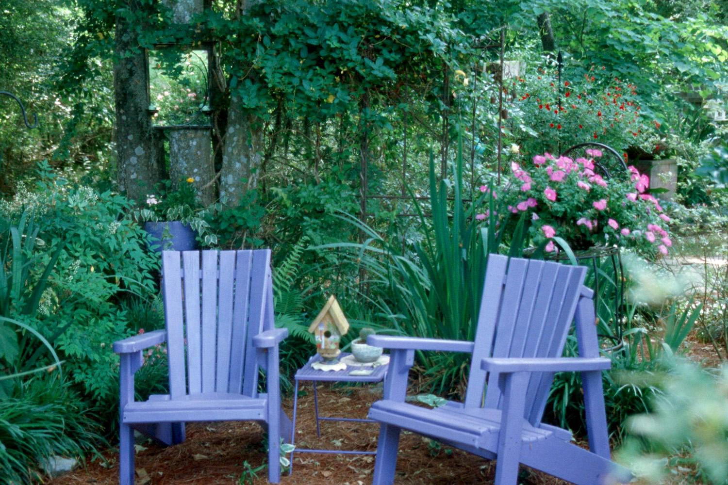The mirror hanging on the tree over the left Adirondack chair blends comfortably into this lovely home-like setting.