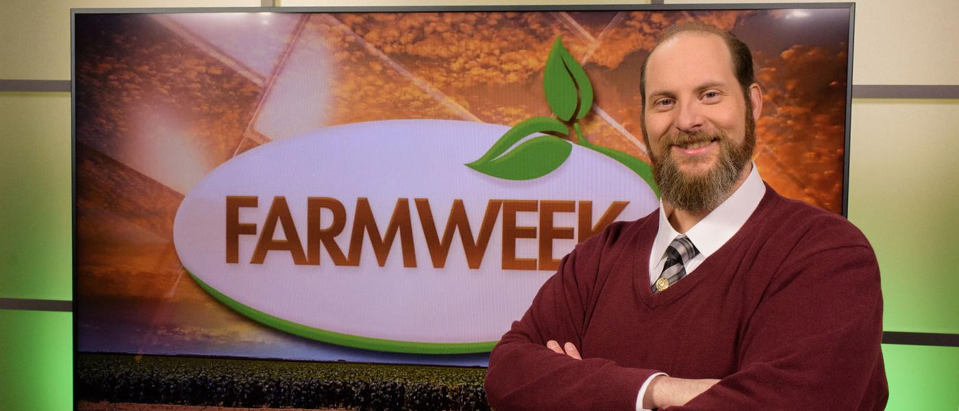A man stands in front of a TV monitor displaying the Farmweek logo.