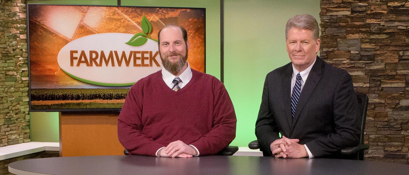 Two men sit at a TV studio desk with Farmweek logo on monitor behind him.