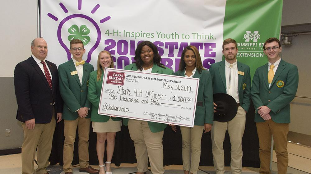 An adult with 4H'ers with a large scholarship check.