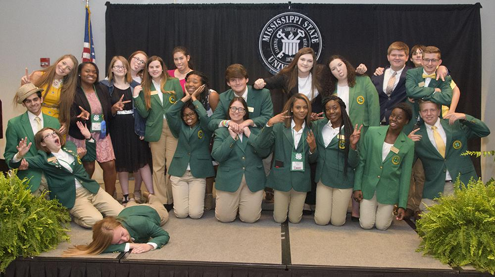 Twenty-one teens, most of whom are wearing green sport jackets, make silly faces for the camera.