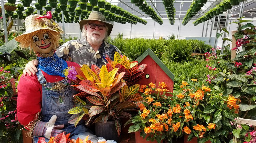 Southern Gardening host Dr. Gary Bachman in greenhouse with scarecrow.