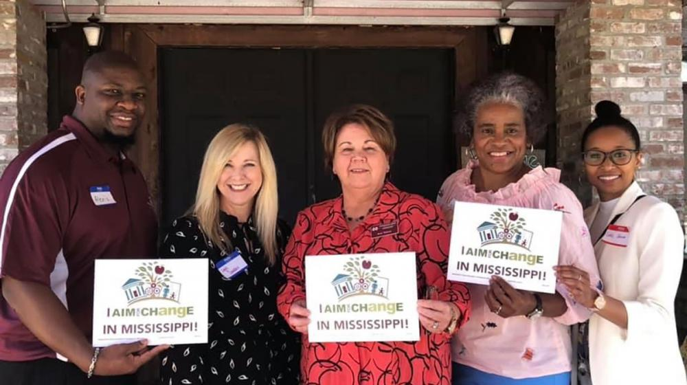 """Four coalition members stand with Extension agent Alexis Hamilton. They hold small signs that read """"I aim for change in Mississippi"""" with the AIM for CHangE logo."""