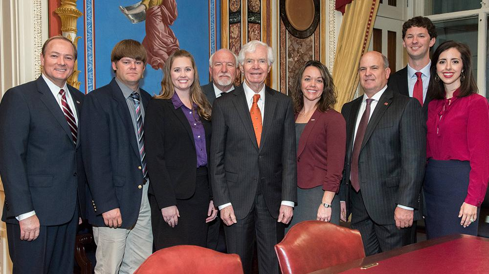 A group of individuals surround Senator Thad Cochran.